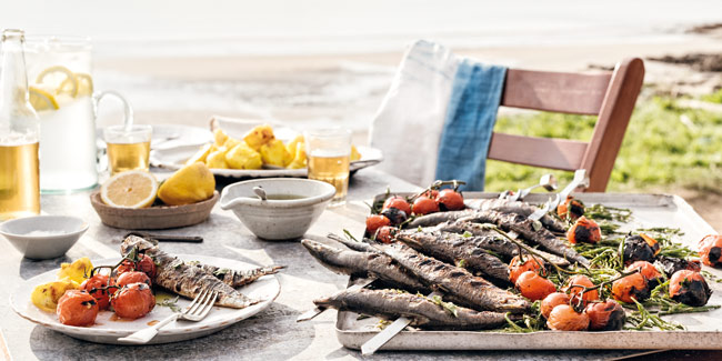 Outdoor feast in summer with sardines and tomatoes