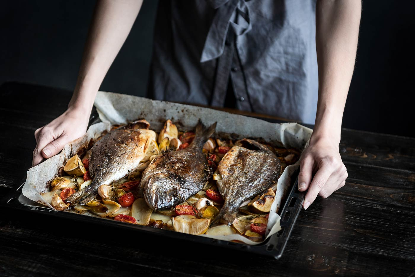 Baked fish being placed on table