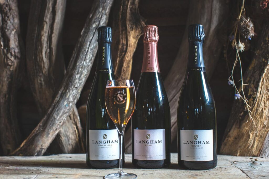 Three bottles and a wine glass of sparkling wine from Langham Wine Estate in Dorset