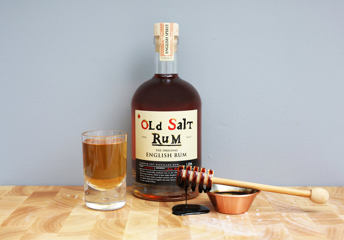 Bottle of Old Salt Rum with shot glass and molasses