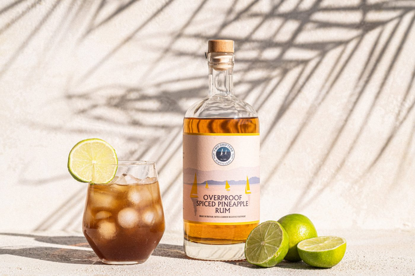 Bottle of Two Drifters pineapple rum with glass and limes
